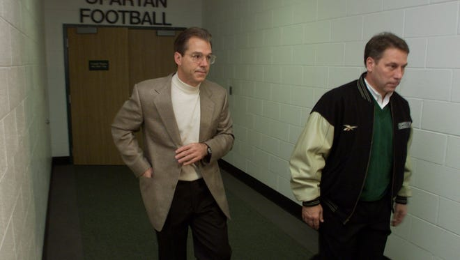 Former Spartan football coach Nick Saban, left, accompanied by Spartan basketball coach Tom Izzo, leaves an early morning team meeting in 1999 at the Duffy Daugherty football building on the East Lansing campus.