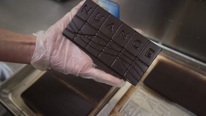 Alix Gadd holds a tempered bar of chocolate at Nuance's production facility on Friday, January 19, 2018. Bars cool in the molds and are soon packaged for customers.