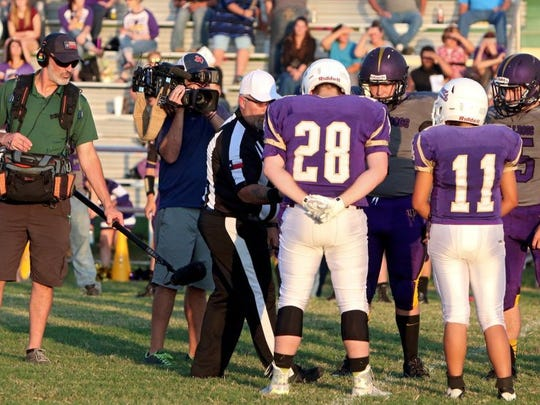 Harrold captains Brady Blakley (28) and Olivia Perez (11) participate in the coin toss last year while ESPN cameras document the game.