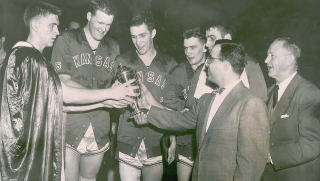 Walt Byers, executive director of the NCAA (2nd from right in suit) presents the trophy to members of the 1952 Kansas team that beat St. John's to win the NCAA tourney.  From left are: Bob Kenney, Clyde Lovellette, Bill Hougland, John Keller, Bill Liennard and coach F.C. Allen.  AP file photo