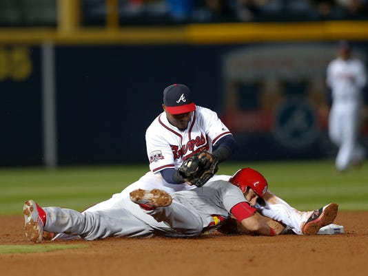St. Louis Cardinals third baseman Matt Carpenter (13) is tagged out at second base by Atlanta Braves shortstop Erick Aybar (1) as he tries to stretch a single in the seventh inning of a baseball game Friday, April 8, 2016, in Atlanta. (AP Photo/John Bazemore)