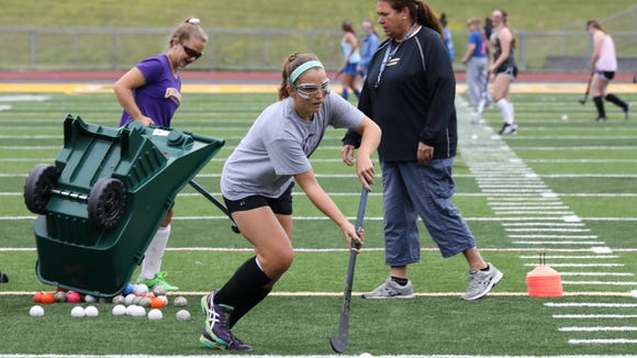 Caroline Cahill, a captain on the Lakeland High School Field Hockey team, moves the ball downfield in front of coach Sharon Sarsen, during a practice at the school, Aug. 29, 2017.