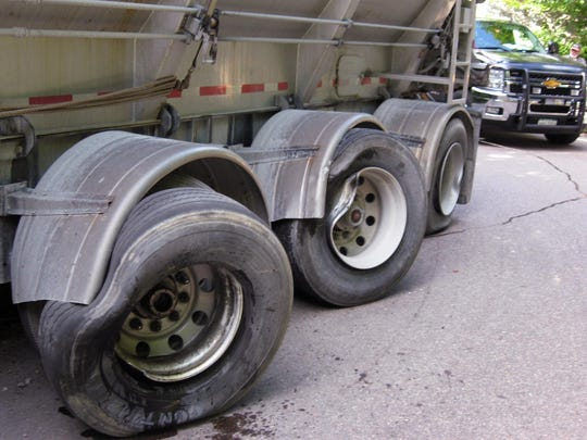 In this Aug. 20, 2014, photograph provided by the Vermont Department of Motor Vehicles, the rear wheels of a truck trailer are damaged as the truck blocks the road and ends up stuck on Vermont 108 in Smugglers/