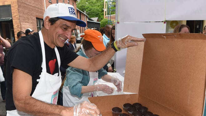 Bernie Zerfas, a volunteer with Lovin From the Oven, opens a box of chocolate cupcakes during K104's Cupcake Festival on Main Street in Beacon.
