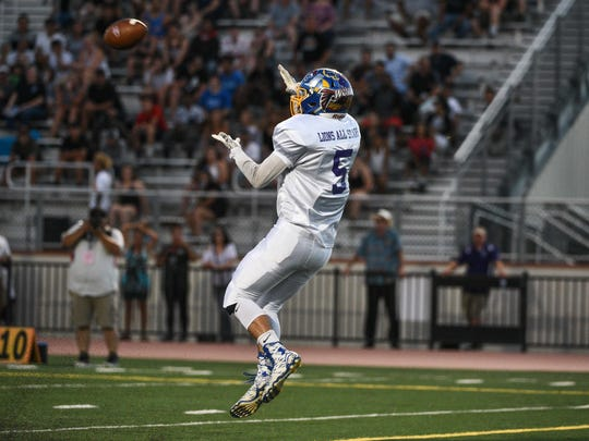 Seth White of Anderson after receiving a catch from Mount Shasta quarterback Thairen Sivongsa at the Lions All-Star Football game at at Harrison Stadium in Oroville.