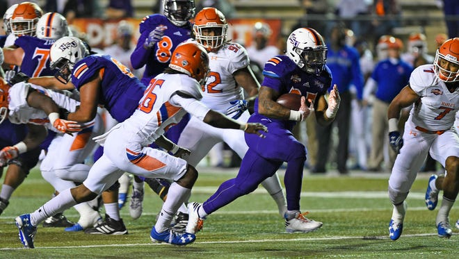 Northwestern State running back De'Mard Llorens runs against the Sam Houston State defense.