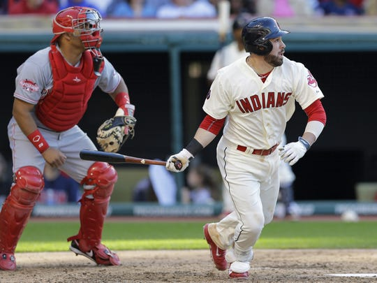 Cleveland Indians Jason Kipnis watches his RBI double off Cincinnati Reds relief pitcher Tony Cingrani in the eighth inning of a baseball game, Saturday, May 23, 2015, in Cleveland. Reds catcher Brayan Pena is at left. The Indians defeated the Reds 2-1.