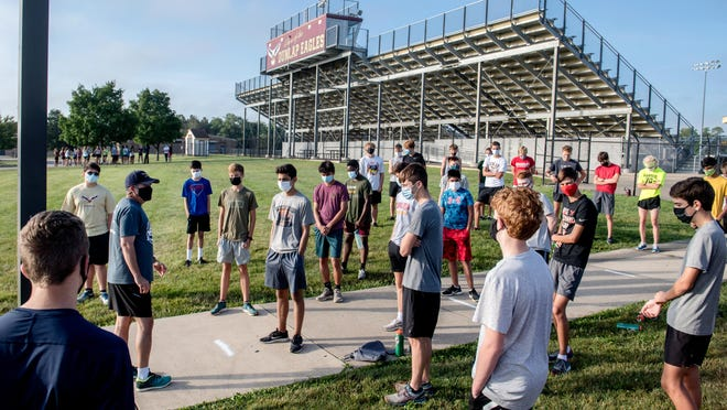 Dunlap cross country coach Chris Friedman, in hat, gives his boys team some guidance at the start of practice Tuesday, Aug. 11, 2020 at the school.