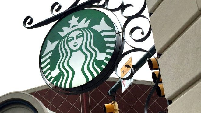 A Starbucks sign hangs from the corner of the Omni Severin hotel in Downtown Indianapolis. The Seattle coffee chain is adding a new location at the 360 Market Square apartment tower.