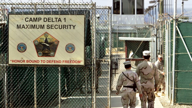 In this June 27, 2006 file photo, reviewed by a U.S. Department of Defense official, U.S. military guards walk within Camp Delta military-run prison, at the Guantanamo Bay U.S. Naval Base, Cuba.