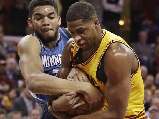 The Minnesota Timberwolves' Karl-Anthony Towns, left, and the Cleveland Cavaliers' Tristan Thompson battle for the ball in the first half Monday in Cleveland.