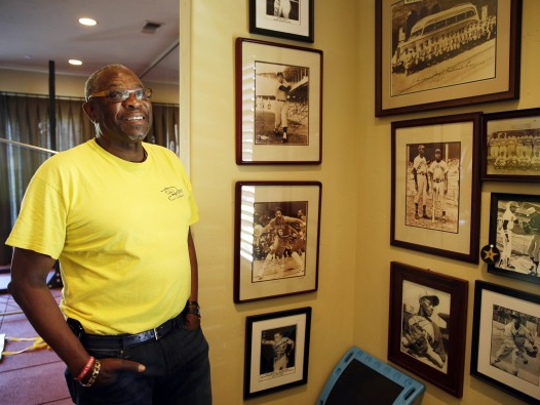 Dusty Baker looks at walls covered with old photographs of players and teams that impacted him in the gymnasium of his home in Granite Bay, Calif.