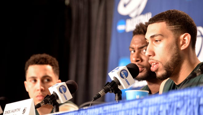 Denzel Valentine, right; fields a question as teammates Travis Trice, left; and Branden Dawson listen.