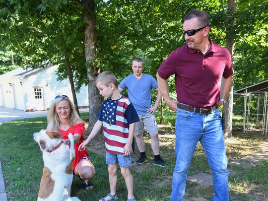 Greenville Chief Deputy John Eldridge plays with the family dog Isaac with his family, from left, wife Amy, and sons Eli and C.J. at their home in Travelers Rest on Wednesday, June 28, 2017. Eldridge will be retiring Friday after 27 years on the force.