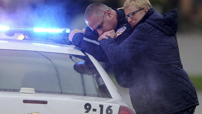 New Kensington Police Chief James Klein and Lisa Shaw, mother of slain New Kensington Police Officer Brian Shaw share a moment while waiting at the Rusiewicz Funeral Home in Lower Burrell for the procession to arrive Saturday, Nov. 18, 2017, in New Kensington, Pa. Shaw was shot in the chest Friday night in New Kensington, northeast of Pittsburgh. The shooting occurred during a foot chase that began shortly after a traffic stop took place. (Pam Panchak/Pittsburgh Post-Gazette via AP)