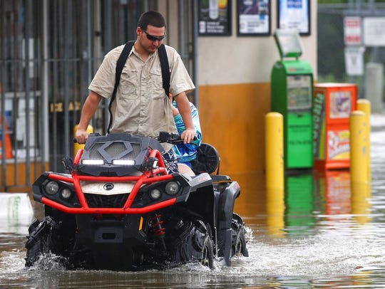 Alexis Obregon drives his ATV through high water on