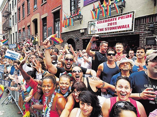 People cheer while standing in front of the Stonewall