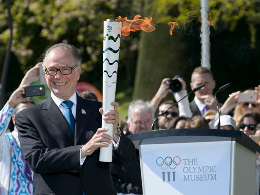 Carlos Arthur Nuzman, Brazil's Olympic Committee President poses with the torch during the Olympic flame welcoming ceremony at the Olympic Museum, in Lausanne, Switzerland, Friday, April 29, 2016. (Anthony Anex/Keystone via AP)