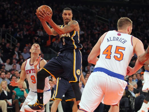 Mar 19, 2014; New York, NY, USA; Indiana Pacers point guard George Hill (3) rebounds against New York Knicks point guard Pablo Prigioni (9) and New York Knicks center Cole Aldrich (45) during the first quarter of a game at Madison Square Garden. Mandatory Credit: Brad Penner-USA TODAY Sports