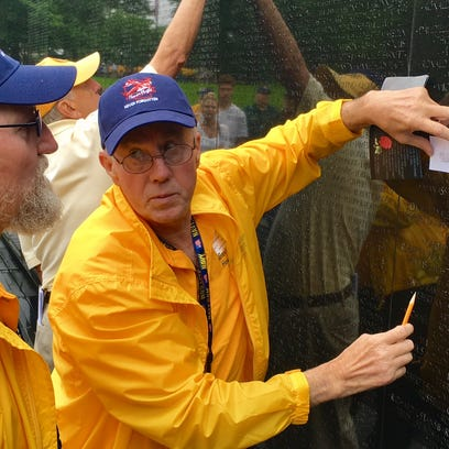 Conrad, left, and Andy Suchon trace the name of their