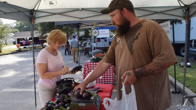 Pam Eggers (left) purchases produce from T.J. Vallery who is selling items for Bill Floyd at the Farmers' Market held in in the parking lot of First United Methodist Church Alexandria Tuesday. City of Alexandria Mayor Jacques Roy read a proclamation announcing Saturday as Food Day.