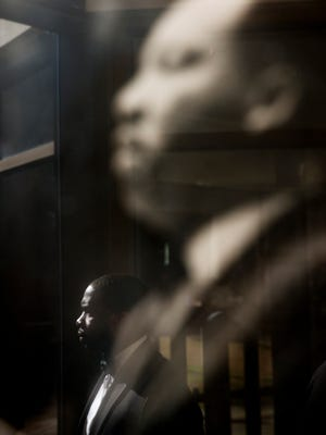 A man is reflected in glass while walking past a photo of the Rev. Martin Luther King Jr. hanging at Ebenezer Baptist Church where King preached, during the King holiday commemorative service Monday, Jan. 18, 2016, in Atlanta.