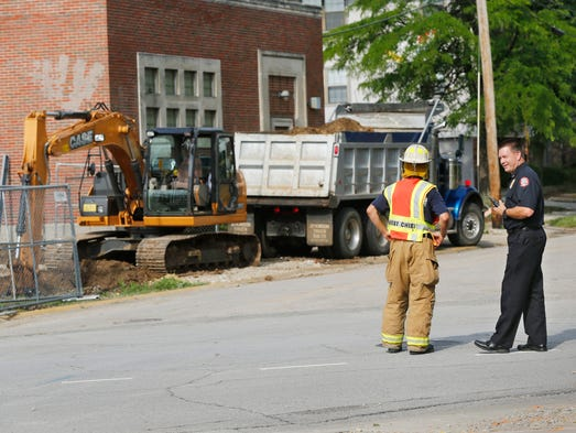 Police and firefighters prevent pedestrian and car traffic from entering the area after a gas line was severed (background left) Thursday, June 19, 2014, near North Street and Northwestern Avenue in West Lafayette.