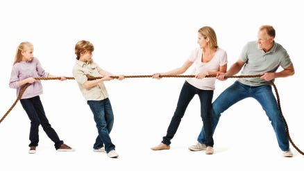 Two children play against their parents in a game of tug o war.