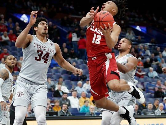 Alabama's Dazon Ingram (12) heads to the basket past