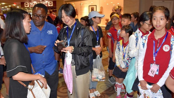 Chinese children and teachers mingle with Middle Tennessee State University President Sidney McPhee, center left in a blue shirt, in 2017.