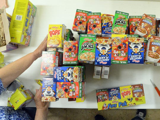 Judy Ackerman stacks small boxes of cereal as she and
