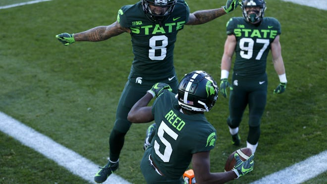 Michigan State's Jayden Reed (5), Jalen Nailor (8) and Tyler Hunt (97) celebrate Reed's touchdown reception against Northwestern during the first half of an NCAA college football game, Saturday, Nov. 28, 2020, in East Lansing, Mich.