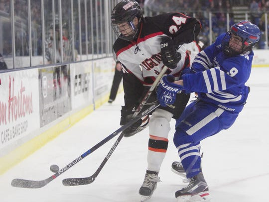 Jake Crespi (24) plays the puck in the state championship