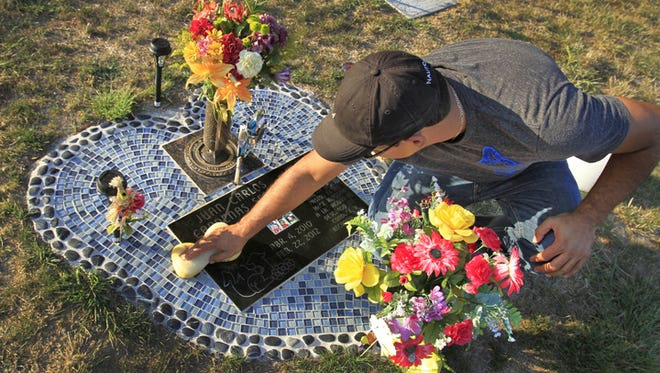 Juan Cardenas visits and cleans the gravesite, Wednesday, September 11, 2013, of his son Juan Carlos Cardenas Serna, who was 22 months old when he died at a church daycare in February 2012. The young child wandered off and drowned in the church baptismal pool.  Cardenas visits his son's grave several times a week.
