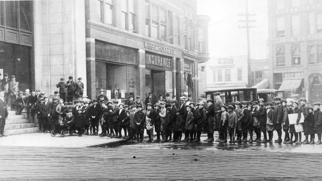 --12-31-99, 6C; Newsboys line up outside the Times Herald offices on Water Street in Port Huron in 1918 while waiting to pick up the extra edition announcing the end of World War I.--EXTRA! EXTRA! Newsboys line up outside the Times Herald offices on Water Street in Port Huron, in the photo above, while waiting to pick up the extra edition that announced the end of World War I. At left, local veterans of the U.S. Army's Red Arrow Division enjoy a chauffer-driven homecoming parade down Huron Avenue in downtown Port Huron in an undated photo. Another hero of World War I was the American Machining Corp. of Port Huron, shown below. The company, at Whipple and Elk street, manufactured munitions for the Russians fighting the Kaiser's troops on the eastern front. BWM