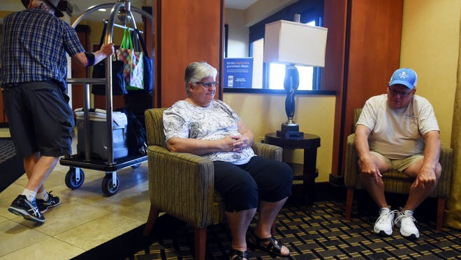 Gene and Jeffrey Vaughan sit in the lobby of the Comfort Suites off I-95 on State Road 60 in Vero Beach as hotel customers move about. The Vaughans have been living in at the hotel for two months, costing more than $7,000, as they wait to move into their newly-built house. The Vaughans built a house in Millstone Landing, but got stuck in the hotel when the county stopped building permits and final inspections because Millstone developers hadn't completed a required road on time.