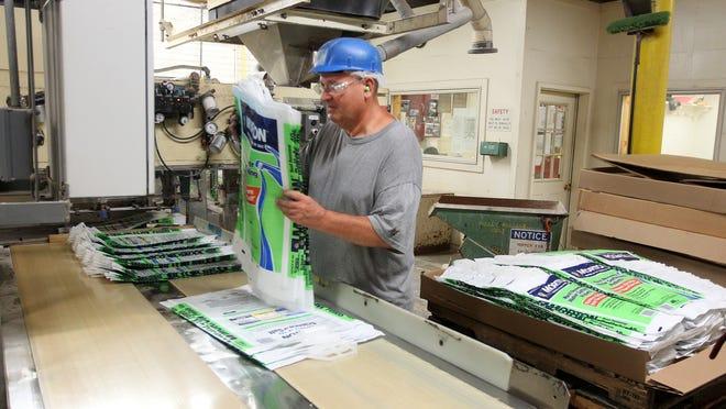 Jerry Szymanski loads a bagging machine for water softener salt at Morton Salt in Silver Springs.