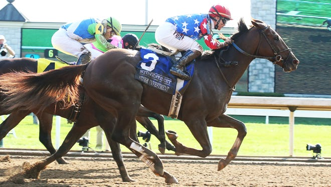 Senior Investment and jockey Channing Hill win Saturday's Lexington Stakes at Keeneland.
