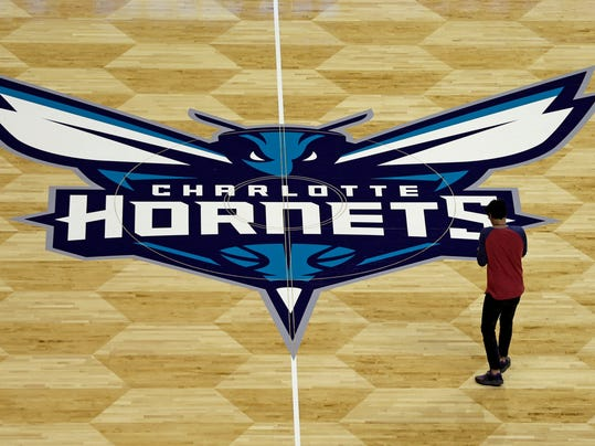 A photographer takes photos of the Charlotte Hornets logo during a news conference to unveil the design for their home court in Charlotte, N.C., Thursday, June 26, 2014. (AP Photo/Chuck Burton)