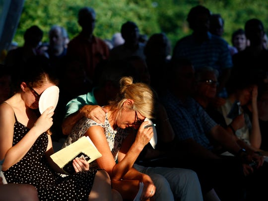 Maria Hiaasen, second from left, widow of Rob Hiaasen, and her daughter Sam, left, react during a memorial service for Rob Hiaasen, one of the journalists killed in the shooting at the Capital Gazette newspaper offices, Monday, July 2, 2018, in Owings Mills, Md.
