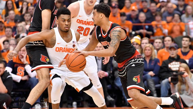 Feb 13, 2017; Syracuse, NY, USA; Louisville Cardinals guard Quentin Snider (right) uses a pick by teammate Louisville Cardinals forward Anas Mahmoud  on Syracuse Orange guard John Gillon (4) and forward Tyler Lydon (20) to move the ball during the second half of a game at the Carrier Dome.