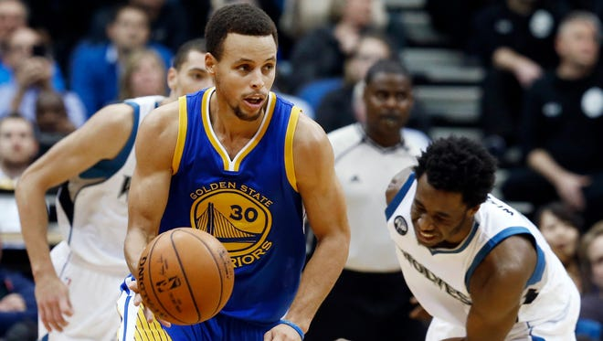 Golden State Warriors' Stephen Curry, left, beats Minnesota Timberwolves' Andrew Wiggins to the ball during the second half of an NBA basketball game, Thursday, Nov. 12, 2015, in Minneapolis. The Warriors won 129-11