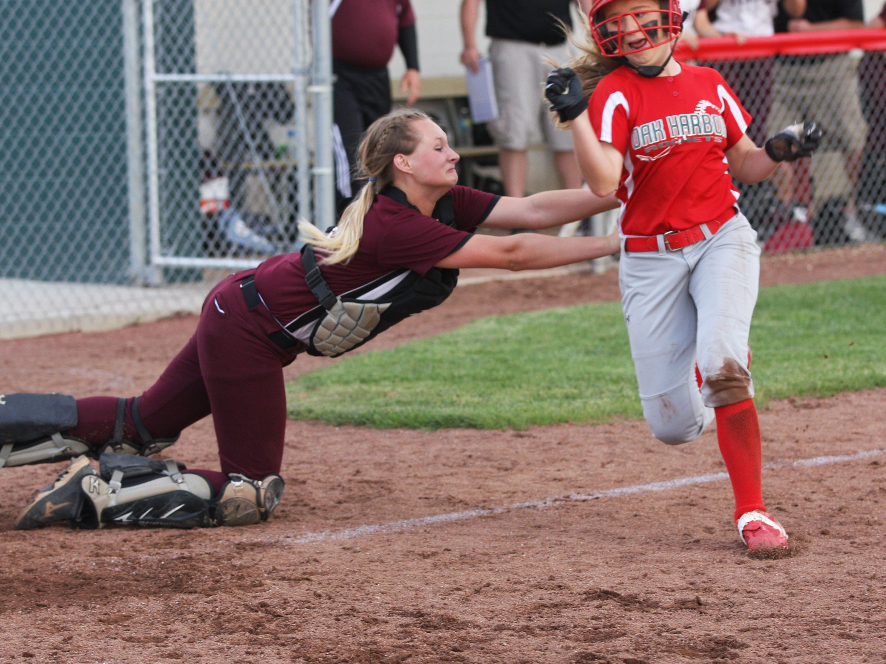 Oak Harbor's Seree Petersen avoids the tag of Willard's Callie Jones to score the game-tying run on a close play at the plate Friday. The Rockets defeated Willard 2-1 in 12 innings in the sectional tournament at Oak Harbor.