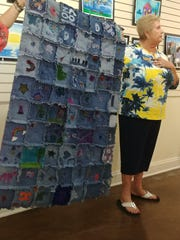 Cape Coral Art Institute teacher show off the children's art project: A piecework quilt on denim that is up for auction. The proceeds will benefit the group's children's program.