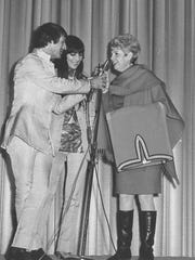 Dorica Wallace presents Sonny Bono with a ruana to match one given to Cher in Austin during the duo's 1967 appearance at the Westwood Theatre in Abilene.