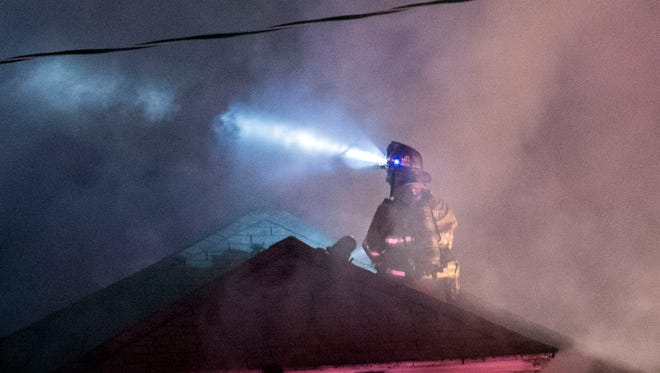 A firefighter works on the roof of a garage fire, Tuesday, October 3, 2017. The fire was reported in the 200 block of East Chestnut Street around 8:14 p.m. According to Met-Ed, there are 1,122 customers without power in Hanover Borough.