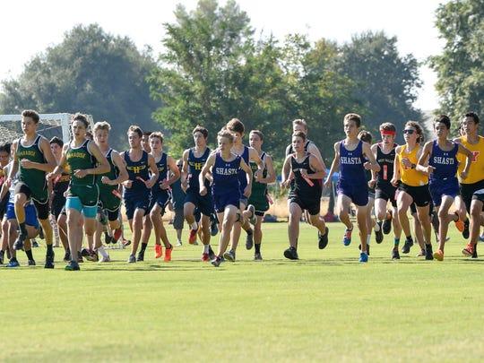 Boys varsity runners leave the starting line Friday