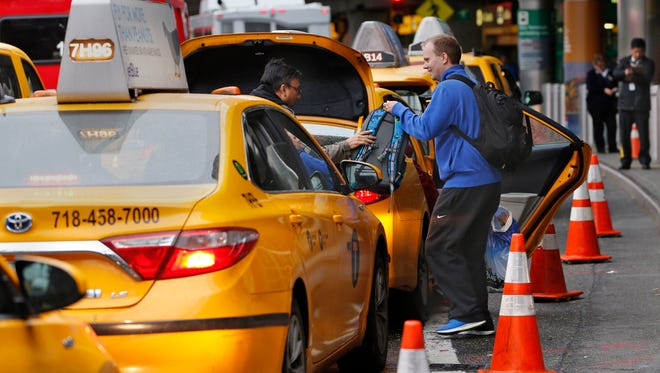 In this Wednesday, May 4, 2016, photo, a driver helps a passenger with his belongings while he and other taxis queue up outside the arrivals area at LaGuardia Airport, in New York. Airports across the country add surcharges of up to $5 a ride, typically passed directly on to travelers, for trips originating at their curbs. There are similar charges for limousine, Uber and Lyft drivers as well as shuttle buses for hotels, car rental companies and off-airport parking lots.