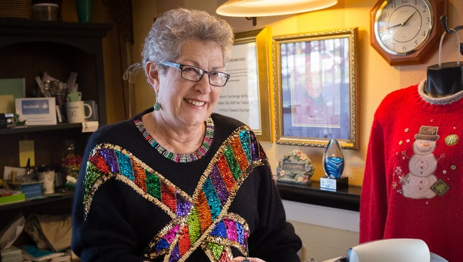 Jackie Hand, a 4-1/2-year volunteer at La Tienda de Jardin Ladies Boutique, models an angora top festooned with sequins. The store has over 50 Christmas-themed tops which are being sold, in addition to the other items in the boutique, to benefit the programs and services for homeless and near-homeless children and families provided by the Jardin de los Niños childcare program.