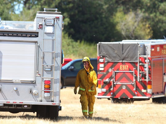 Firefighters control a 10 to 15 acre wild land fire on Tuesday, July 28, 2015, in Salem, Ore.